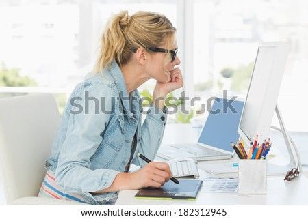 Blonde pretty designer using digitizer at her desk in creative office - stock photo