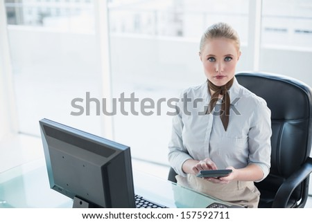 Blonde serious businesswoman using calculator in bright office