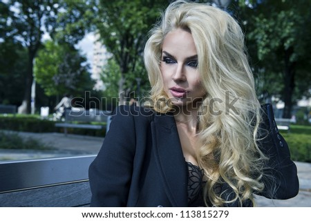 Blonde sexy beauty posing on bench - stock photo