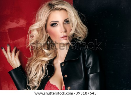 Blonde sexy lady with glamour makeup and long curly hair posing in studio. Elegant woman wearing red sensual lingerie. - stock photo