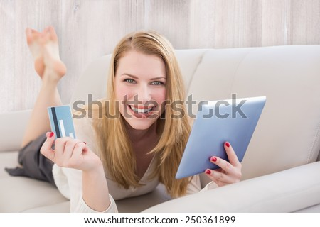 Blonde shopping online against wooden planks - stock photo