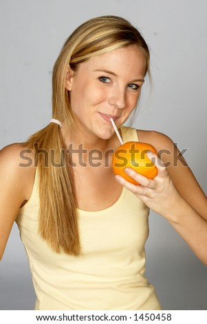 Blonde Sipping Juice from Orange - stock photo