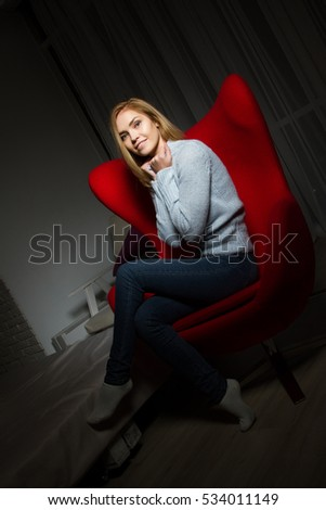blonde sits in a red chair in a dark room