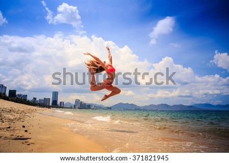 blonde slim female gymnast in red bikini in flying jump with bent backward knees over sea edge on beach against clouds - stock photo