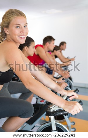 Blonde smiling at camera during exercise class at the gym