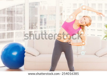 Blonde smiling at camera while stretching against fitness interface - stock photo