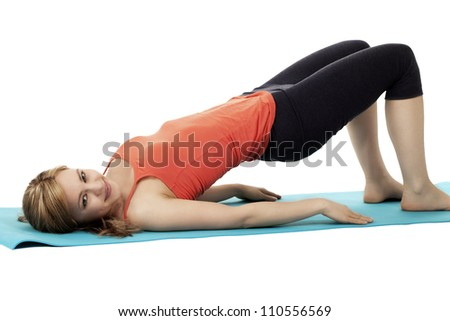 blonde smiling fitness woman exercising on a blue mat on white background - stock photo