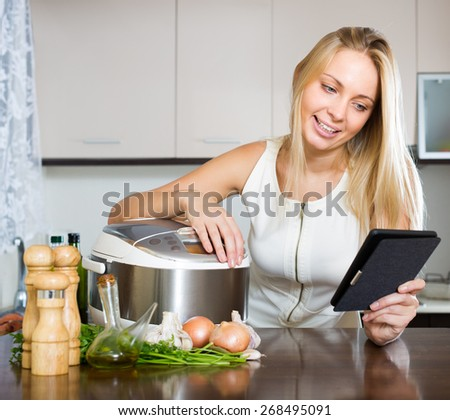 Blonde smiling girl reading ereader while with new electric multicooker doing food at home  - stock photo