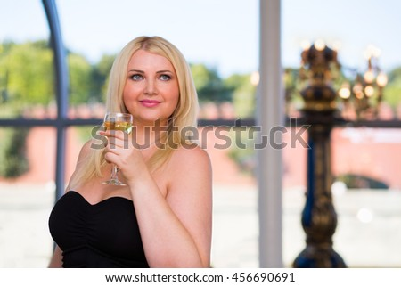 Blonde smiling woman stands in ship restaurant and holds wine glass - stock photo