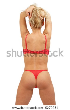 Blonde sportive girl in sexy red lingerie stands with hands up and her back turned toward us - stock photo