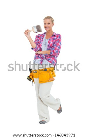 Blonde standing while holding a paint brush on white background - stock photo