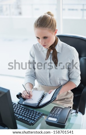 Blonde stern businesswoman writing in diary in bright office