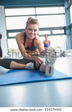 Blonde stretching her legs in gym - stock photo