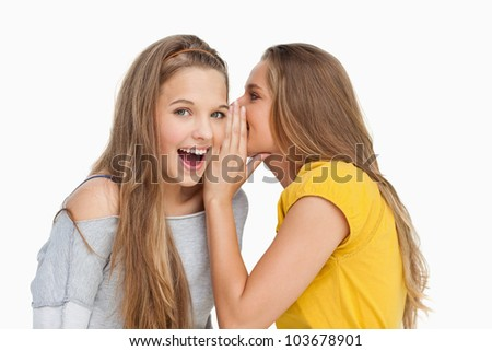 Blonde student whispering to her friend against white background - stock photo