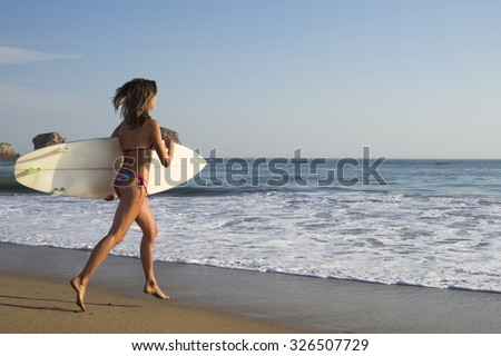 Blonde surfer girl run in bikini on the beach to the sea with a surf board, surfing - stock photo