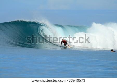Blonde surfer in orange shirt on big wave, Mentawai Islands, Indonesia - stock photo