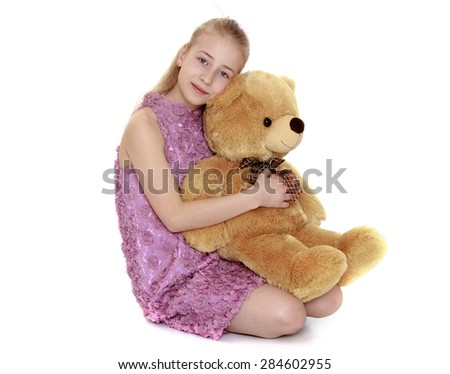 Blonde teen girl hugging a big Teddy bear- isolated on white background - stock photo