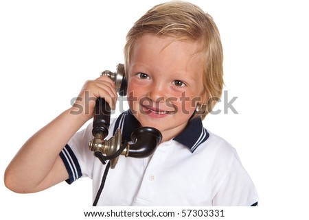 Blonde toddler boy playing with a black antique telephone - stock photo