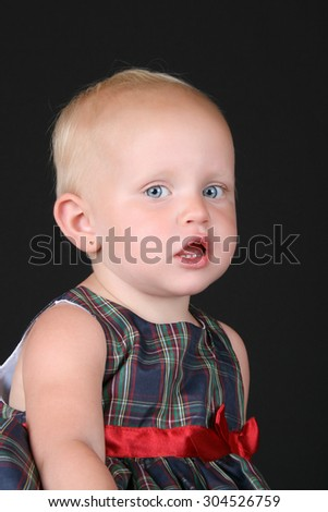 Blonde toddler girl wearing a christmas dress against black - stock photo