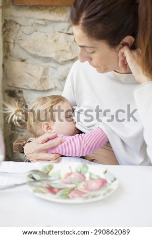blonde two years age baby with pigtails breastfeeding woman mother white jersey sitting in restaurant table - stock photo