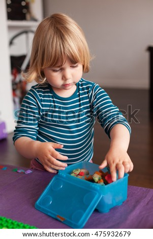 blonde two years old child with striped blue and white sweater inside home storing  plasticine in blue plastic box on purple table