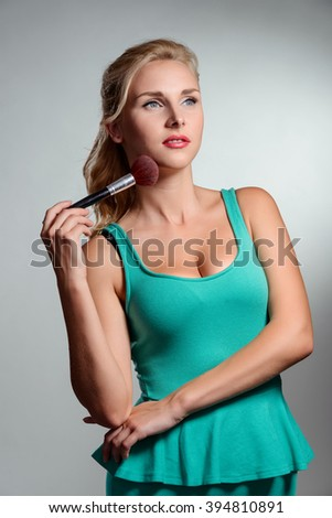 Blonde who loves her profession. Make-up artist with a brush. Beautiful woman in green top. - stock photo