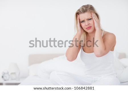 Blonde with a headache sitting on her bed - stock photo