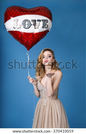 Blonde with a red heart in an elegant evening dress. Valentines Day. Love. Fashion beautiful woman with red heart balloon on a blue background. Beautiful bride in wedding day making a kiss - stock photo