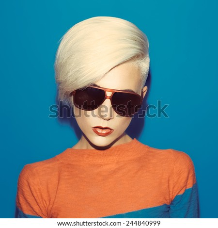 Blonde with fashionable Hairstyle and Sunglasses on blue background - stock photo