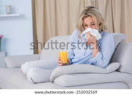Blonde with glass of orange juice and sneezing at home in the living room