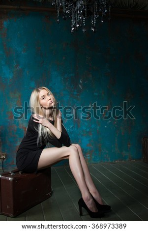 blonde with long legs sitting on a suitcase