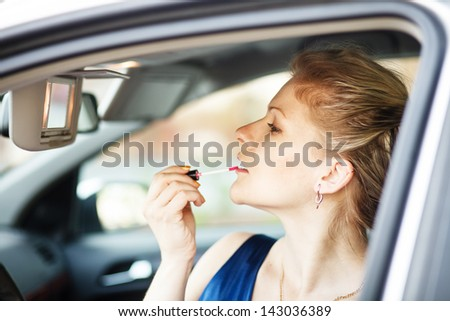 Blonde woman applying make-up in a car. - stock photo