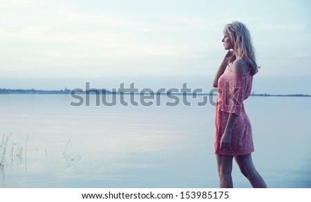 Blonde woman at the lake - stock photo