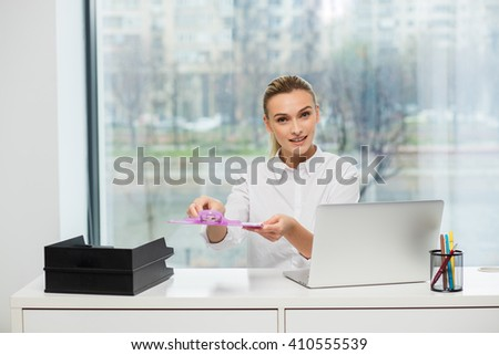 blonde woman behind her desk with clipboard in her hands offering a contract to be signed - stock photo
