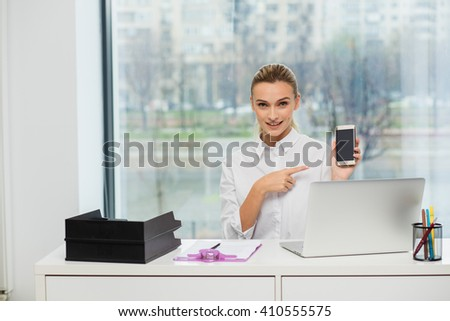 Blonde woman behind her desk, working and making phone calls, pointing the cellphone - stock photo