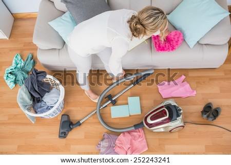 Blonde woman cleaning her chaotic living room at home - stock photo
