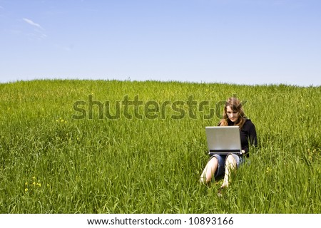 Blonde woman connected to the internet in a meadow - stock photo