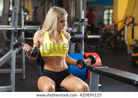 Blonde woman doing  workout with dumbbells at the gym - stock photo