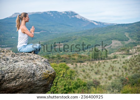 Blonde Woman Doing Yoga at the Mountains - stock photo