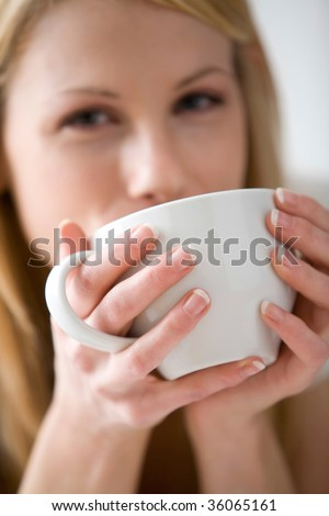 Blonde woman drinking from a white mug and looking at the camera - stock photo