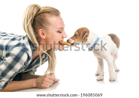 Blonde woman eatting one biscuit with Jack Russell Terrier puppy isolated on white background - stock photo