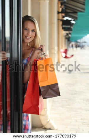 blonde woman entering in a store - stock photo