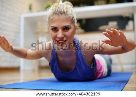 Blonde woman exercise at home.  Looking at camera.