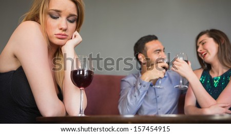 Blonde woman feeling envious of two people are flirting beside her in a nightclub - stock photo