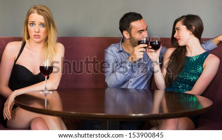 Blonde woman feeling jealous as two people are flirting beside her in a club looking at camera - stock photo