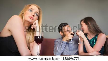 Blonde woman feeling jealous of two people are flirting beside her in a nightclub - stock photo