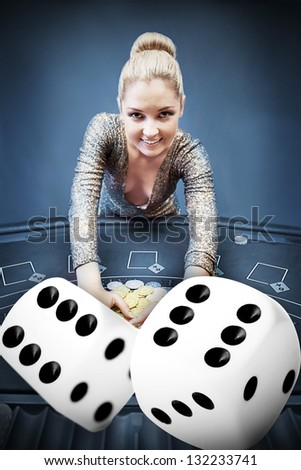 Blonde woman grabbing chips with digital dice in blue tint - stock photo