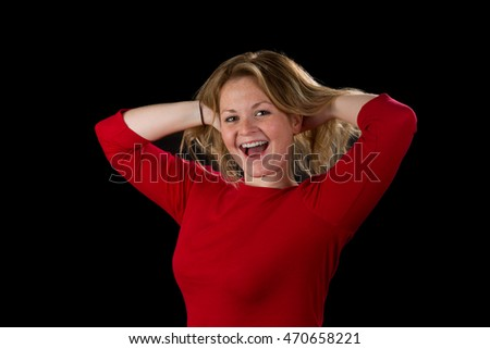 Blonde woman happily pulling her hair up