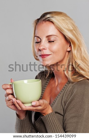 Blonde woman holding a cup of tea and tasting the smell isolated on grey