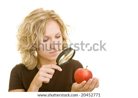 Blonde woman holding a magnifying glass and an apple - stock photo